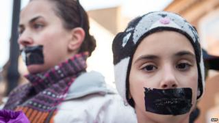 Demonstrators wear tape over their mouths as they protest outside the Egyptian embassy in central London on 29 December 2014 to mark the one-year anniversary of the arrest of three al-Jazeera journalists in Egypt.