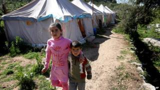 Syrian refugees walk next to their tents at a small refugee camp in the village of Ketermaya, southeast of Beirut, Lebanon.