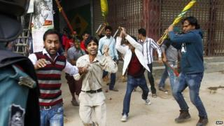 A Bangladeshi policeman (left) looks on as government party activists (right) wield sticks against activists of the Bangladesh National Party (BNP) during a clash in Dhaka (05 January 2015)