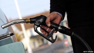 A customer pulls the nozzle of a petrol