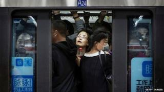 Chinese commuters crowd onto a subway car on the metro during rush hour on October 16, 2014 in Beijing,