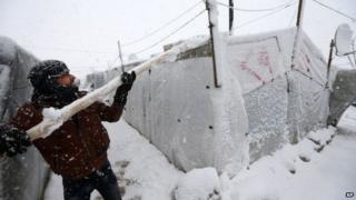 A Syrian refugee uses a pole to try to clear snow from the roof of his tent in Deir Zannoun village, in the Bekaa Valley, east Lebanon (7 January 2015)