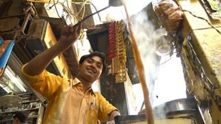 A chai wallah doing acrobatics with a steaming infusion