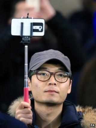 A football fan uses his selfie stick to hold aloft his smartphone