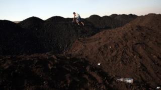 An Indian man climbs a mound of coal at a coal yard in Mumbai, India, Wednesday, Jan. 7, 2015.