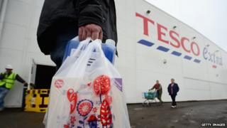 Man with Tesco bag walks past side of Tesco Extra store in Glasgow