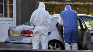 Forensic investigators examine a car at the scene of the murder