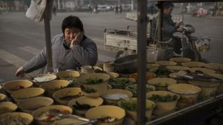 A Chinese food vendor waits for customers at a market on November 21, 2014 in Hebei just outside Beijing, China