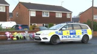 Police car and floral tributes outside the house in Durrington