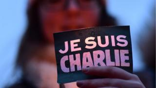 A woman holds a 'Je suis Charlie' sign