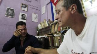 Angel Figueredo (right), Cuban activist released, holds his son's hand