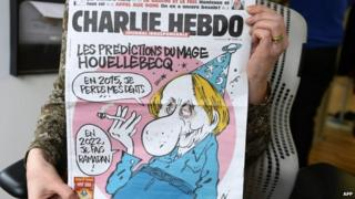 A person holding the front page of Charlie Hebdo magazine.