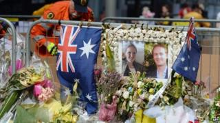A volunteer removes flowers next to a photo showing Katrina Dawson and Tori Johnson at a memorial site outside the Lindt cafe in Sydney on December 23, 2014