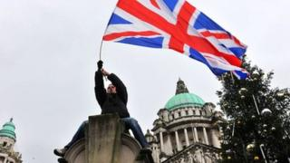 A man waves a union flag during a protest outside Belfast City Hall