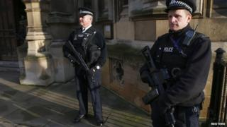 Armed police officers stand on duty outside the Houses of Parliament in Westminster, central London November 24, 2014