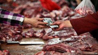 People purchase pork at a market on May 9, 2013 in Nantong, China.
