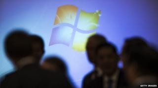Microsoft Windows logo behind shadowed crowd