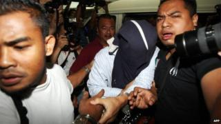 Malaysian security officers carry away one of the policemen (C) with covered face found guilty in a Mongolian model girl murder case, at Shah Alam high court outside Kuala Lumpur on 9 April 2009.
