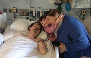 Alex in hospital with Lucy and his son