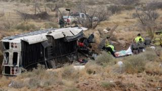 Officials investigate the scene of a prison transport bus crash in Penwell, Texas 14 January 2015