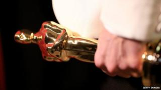Oscar statue in hand