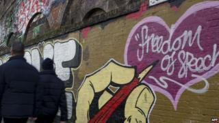 Pedestrians in London walk past a wall with freedom of speech scrawled on it