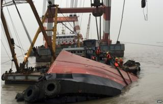 "Members of a rescue team (orange) look at a section of the hull (front C) of a tugboat which sank on a trial voyage in Jingjiang, east China""s Jiangsu province on 16 January 2015."