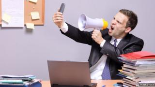 man uses megaphone to shout at phone