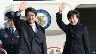 Japanese Prime Minister Shinzo Abe (left) and his wife Akie wave to well-wishers upon their departure at Tokyo's Haneda airport, 16 January 2015