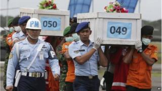 Members of the National Search and Rescue Agency carry coffins containing bodies of the victims aboard AirAsia Flight 8501 to transfer to Surabaya at the airport in Pangkalan Bun 19/01/2015