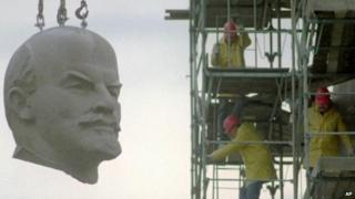 The huge granite head of Berlins Lenin statue is hanging at a crane during its dismantling in Berlin November 13, 1991.