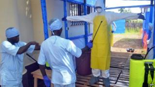 Health workers wash a colleague by spraying them at the Ebola Transit Center in Forecariah