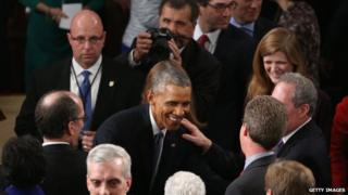 President Barack Obama greets members of Congress after delivering the State of the Union address in the House chamber