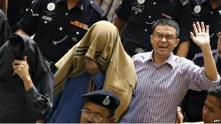 Charged political analyst Abdul Razak Baginda (R) waves to photographers as he and charged special unit police officers Sirul Azhar Umar (C) and Azilah Hadri (L) cover their faces while being escorted out of court during an intermission in Shah Alam, near Kuala Lumpur, 29 June 2007