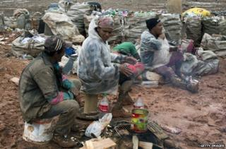 Pickers take a break among the rubbish