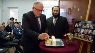Vice-President of the European Commission Frans Timmermans, left, lights a memorial candle during a memorial service at the European Jewish Association in Brussels, 21 January