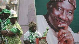 A woman sits beside an electoral poster of Nigeria's President Goodluck Jonathan during the flag-off for his campaign for a second term in office, in Lagos on 8 January 2015
