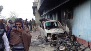 A burnt-out car is seen in front of a charred house following communal riots in the north-western Indian state of Bihar on 19 January 2015.