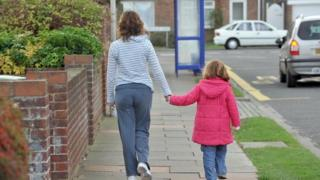 mother walking down street hand-in-hand with daughter