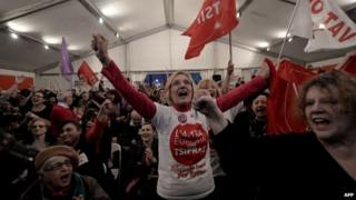 Anti-austerity Syriza supporters celebrate after the first exit polls, as they gather at the Syriza election kiosk in Athens on January 25, 2015