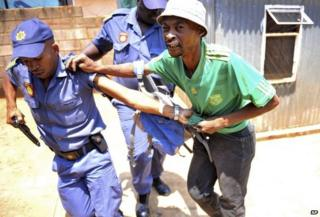 Police arrest a man suspected of looting a store in Soweto, South Africa on 22 January 2015