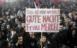 """Syriza supporter holds up placard in Athens saying """"This is a really good night, Mrs Merkel"""""""