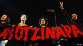 "Women hold banner and yell slogans in support of the 43 missing trainee teachers of the Ayotzinapa teachers"" training college, during a protest at the International Santa Fe bridge and border crossing between Mexico and the U.S. in Ciudad Juarez 26 Jan 2015"