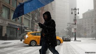 A man walks through the snowy streets of New York City.