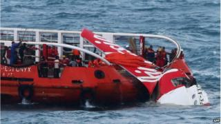 In this file photograph taken on 10 January 2015, Indonesian search and rescue personnel pull wreckage of AirAsia flight QZ8501 onto the Crest Onyx ship at sea.