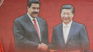 A poster shows Venezuelan President Nicolas Maduro shaking hands with China's President Xi Jinping during a signing-of-agreements ceremony in Caracas on 21 July, 2014.