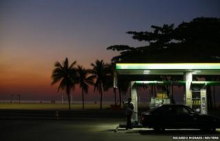 A worker prepares to fill a car at a gas station close to Copacabana beach in Rio de Janeiro