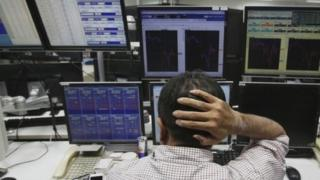 An employee in Tokyo reacts as he works in front of monitors displaying fluctuations of the exchange rates of major currencies