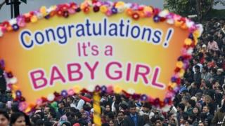 """Indian spectators watch as a float carrying a sign that reads """"Congratulations! It's a Baby Girl"""" passes by during the Indian Republic Day parade in New Delhi on January 26, 2015."""
