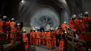 """Workmen look on as tunnel machine, named Elizabeth, breaks through into the east end of Crossrail""""s Liverpool Street station"""